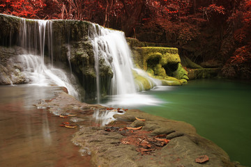 waterfall with clear green emerald water and rock for relax with red tree and root in the jungle at Huay Mae Khamin waterfall for nature landscape and background