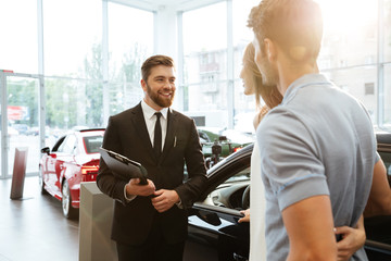 Smiling salesman showing new car to a couple