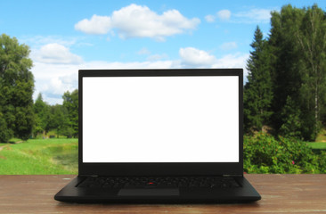 Image of outdoors with open laptop and empty white screen for copy space