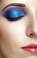 Shot of female half face with closed eye and violet -  blue makeup