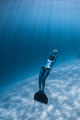 Wall Mural - Woman freediver relaxes underwater with monofin over sandy bottom