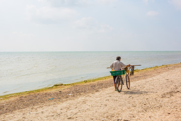 Seller of fish sells fish on the beach by bike