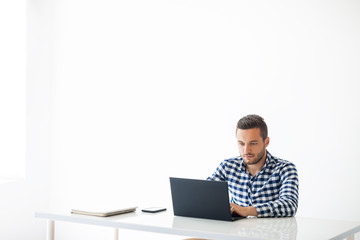 Portrait of handsome man typing on laptop on white background