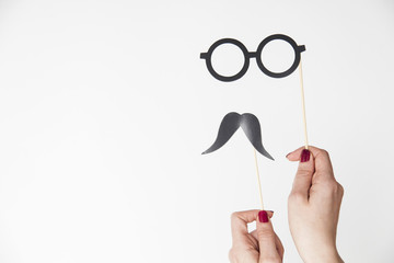 female hand holding glasses and mustache photo booth prop