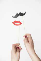 female hand holding mustache and lips photo booth prop