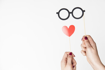 female hand holding glasses and heart photo booth prop
