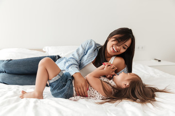 Happy asian woman playing with her little daughter on bed