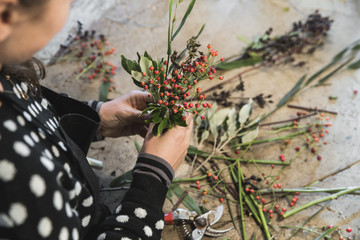 Woman's hands working on an autumn flower arrangement