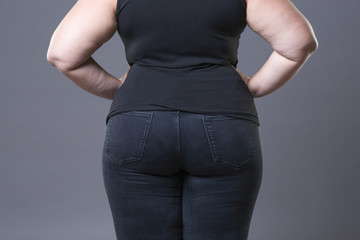 Fat female buttocks in blue jeans, overweight woman body closeup