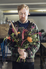 Man holding a flower bouquet evaluating the outcome