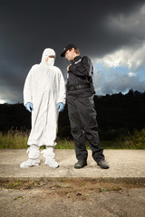 Police man cooperating with criminologist technician