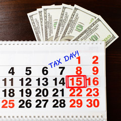 dollars money, April 15 on calendar and Tax Day phrase, wooden background, top view. National Tax Day and financial concept