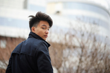 Asian young man in a coat on the street