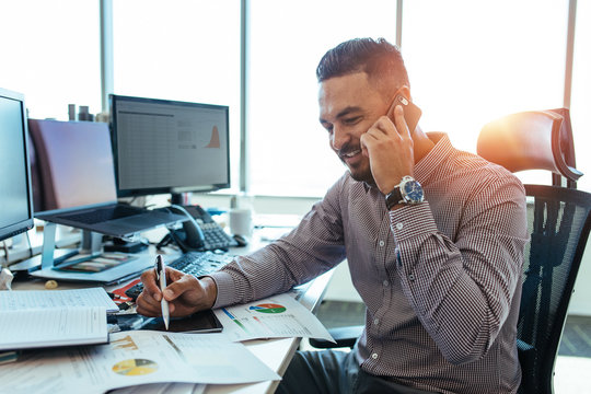 Entrepreneur discussing work over mobile phone sitting at his of