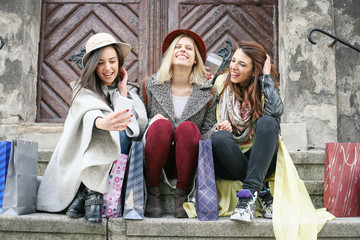Three best friends enjoying after shopping. Three young girls making self-portrait on the stairs after shopping.