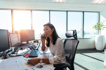 Businesswoman speaking over phone in office.