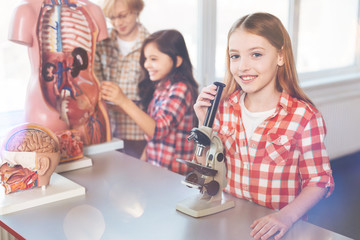 Positive delighted girl standing near microscope