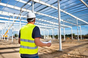 Fototapeta Kierownik budowy hali produkcyjnej stalowej z planem w rękach obraz