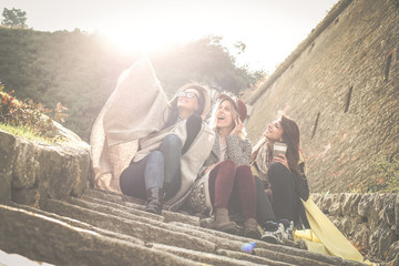 Three young girls sitting on the stairs at the public park. Three best friend making self picture in the public park. Girls sitting on stairs.