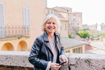 Mature woman holding smartphone in city, Siena, Tuscany, Italy