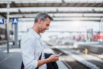 Mature man standing on station platform, looking at smartphone