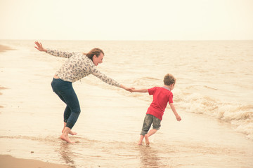 Boy pulling mother toward sea from beach