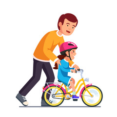 Caring dad teaching daughter to ride bike