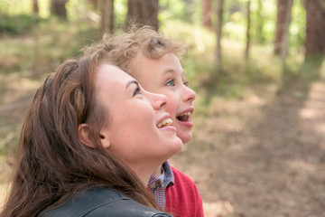 Young woman and son looking up together from woods