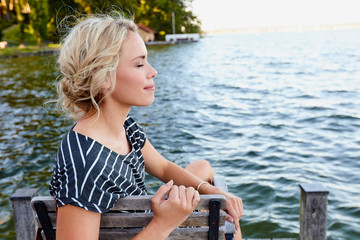 Woman sitting on pier by water