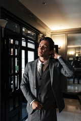 Handsome middle aged businessman in suit standing in a lobby