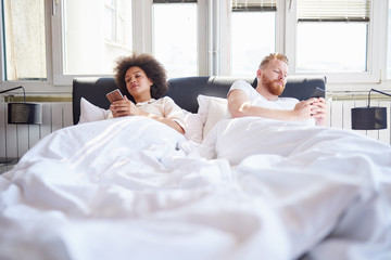 Young couple using mobile phones and lying in bed while ignoring each other