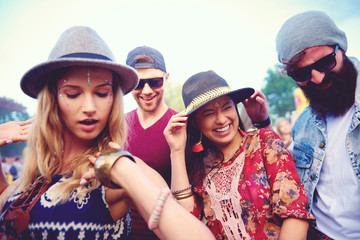 Four young adult friends in fedoras dancing at festival