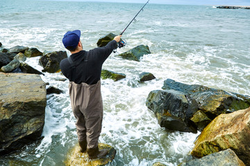Young man standing on rock sea fishing