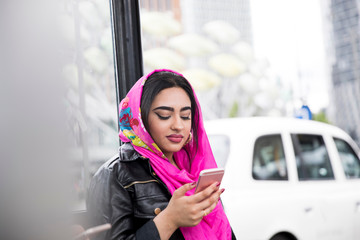 Young woman waiting at bus stop, using smartphone