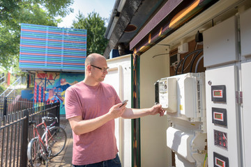Community worker using smartphone app to check heat pump energy