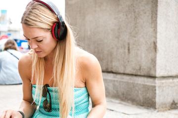 Mid adult woman, outdoors, wearing headphones, looking down