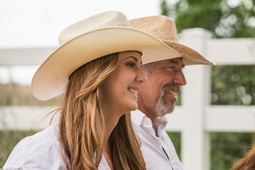 Mature man and young adult daughter in cowboy hats on ranch, Bridger, Montana, USA