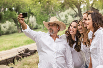 Mature man taking smartphone selfie with women on ranch, Bridger, Montana, USA