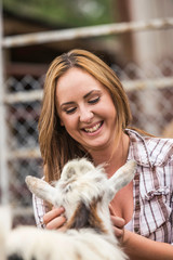 Young woman petting goat, smiling