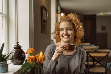 Smiling woman with coffee cup in cafe