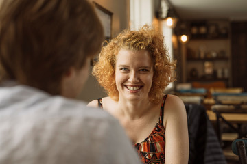 Woman smiling at man in cafe
