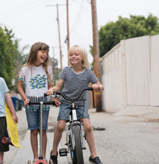Girl and boys in lane with scooter, bicycle and skateboard