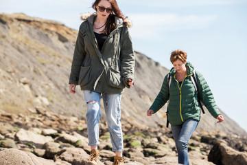Mother and daughter walking by seaside, Folkestone, UK