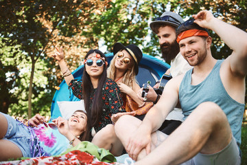 Five young adult friends playing acoustic guitar while festival camping