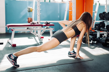 Fitness woman stretching full body over gym background.
