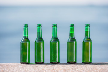 close up view of bottles of beer standing in line on parapet
