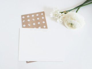 Styled stock photo. Feminine digital product mockup with buttercup and daffodil flowers, and blank list of paper . White background. Flat lay, top view.