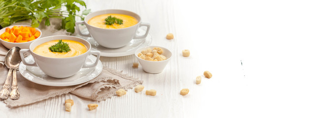 Pumpkin cream soup with croutons, raw fresh pumpkin pieces and herbs on a white rustic wooden background, Autumn concept. Long web format, banner