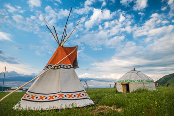 Teepee and yurt set on the green meadow with blue sky on the background