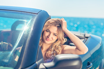 Beautiful blond smiling young woman in convertible top automobile looking sideways while parked near ocean waterfront